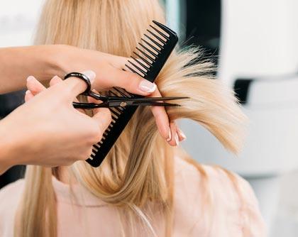 Haarschnitt an blonde junge Dame